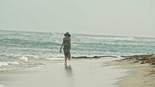 Young woman In long Dress keeps shoes and Walking along the sea, slow-motion