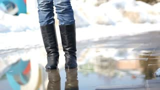 Young woman in rain boots jumping on a puddle