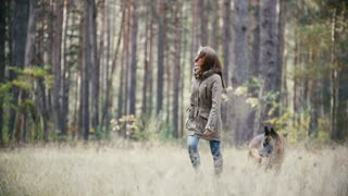 Young woman running with a shepherd dog in autumn forest, slow motion