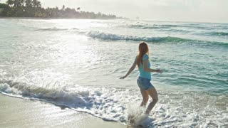Young woman with long red hair in shorts pants play with waves running, feeling the sea, seascape, beach of Dominican Republic