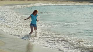 Young woman with long red hair play with waves running, feeling the sea, seascape beach of Dominican Republic
