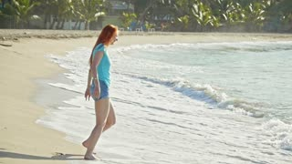 Young woman with long red hair play with waves running, feeling the sea, seascape, telephoto, slow-motion, beach of Dominican Republic,