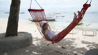 Adorable little girl on tropical vacation relaxing in hammock.Young girl lying in a hammock on the beach and watching the tropical sea.Travel concept.Family,summer vacation.Happy family