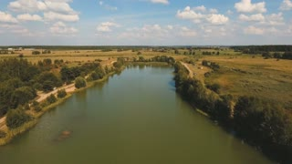 Aerial View. Flying over the lake and green fields. 4K video,ultra HD