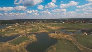 Aerial view of golf green and protective sand trap. Golf course on the background of blue sky and clouds. Aerial view of a beautiful green golf course. 4K video