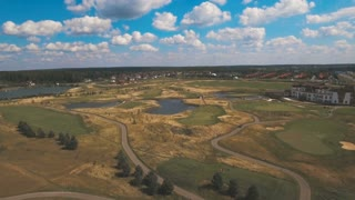 Aerial view of golf green and protective sand trap. Golf course on the background of blue sky and clouds. Aerial view of a beautiful green golf course. An aerial view of the golf course on a summer