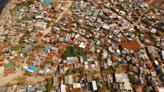 Aerial view poor district of Manila's slums, ghettos, wooden old houses, shacks. Aerial footage slum area of Manila, Philippines. Manila suburb, view from the plane. 4K video