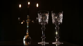 Arm pours wine from a bottle into a beautiful wine glasses.Red wine bottle, two wine glasses,burning candles in a chandelier.Wine glasses on the table, a bottle of red wine and burning candles in a