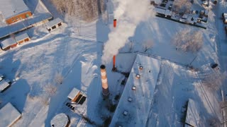 Boiler room in the winter season, from the chimneys rise up clouds of steam. Pipes of a thermal power plant. Boiler house, pipe plant, boiler plant. Aerial footage, 4K video