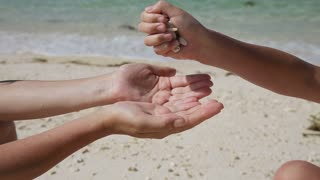 child hand pours in his mother's hands seashells.Hands holding seashells and pour them.In the background, a tropical sea with waves and sand.Travel concept.Family,summer vacation.Happy family