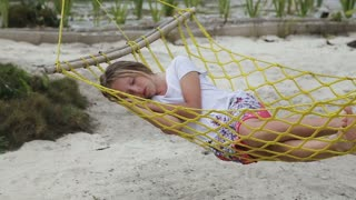 Child sleeps in a hammock on a tropical beach under the palm trees. young girl sleeps in a hammock having enclosed hands under the head