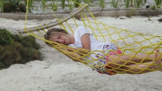 Child sleeps in a hammock on a tropical beach under the palm trees.young girl sleeps in a hammock having enclosed hands under the head