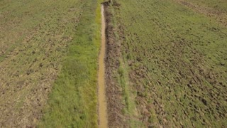 Excavator is digging an irrigation canal. Aerial view:Excavator digging a deep trench. excavator is digging an drainage canal in the agricultural field. 4K,UHD