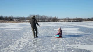 Father with his daughter are traveling on the frozen lake ice skating and sledding.Happy family with child are sledding on the frozen lake.Outdoor winter fun for family.nice winter scene