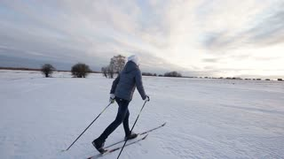 Girl on cross-country skis in the field. Skiing in field in cold winter day. Cross-country skiing on field in the warm day