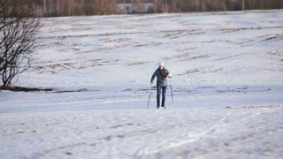 Girl on cross-country skis in the field.Skiing in field in cold winter day.Cross-country skiing on field in the warm day