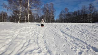 Girl sledging down hill, bright and joyful winter scene.Happy girl expressing joy while sledding in the snow in the winter.Yong girl sledging down hill.Outdoor winter fun for family.nice winter scene