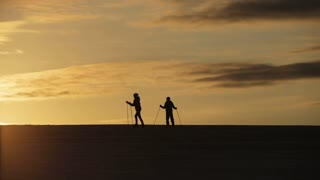 Girls on cross-country skis in the field. Skiing in field in cold winter day. Cross-country skiing on field in the sunny day. Skiers, cross-country skiing in the field at sunset. Silhouette of skiers