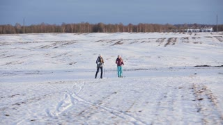 Girls on cross-country skis in the field. Skiing in field in cold winter day. Cross-country skiing on field in the warm day
