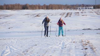 Girls on cross-country skis in the field.Skiing in field in cold winter day.Cross-country skiing on field in the warm day