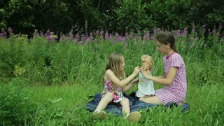 Girls play with dolls on grass.Young children play with dolls in the grass outdoors behind the girls beautiful flowers
