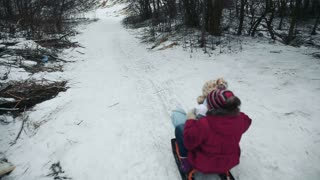 Girls sledging down hill, bright and joyful winter scene.Happy girls expressing joy while sledding in the snow in the winter.Yong girls sledging down hill.Outdoor winter fun for family.nice winter