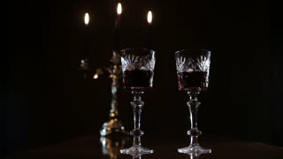 Hands take glasses of wine.Two wine glasses,burning candles in a chandelier.Wine glasses on the table,and burning candles in a beautiful chandelier behind on a black background.Romantic atmosphere