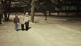 Happy family, going wintertime to slide, family fun outdoor.Mother and daughters walking in the winter, night park.Family walk in a winter park.Family with ice skates.Outdoor winter fun for family