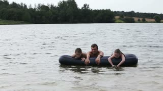Happy family has a rest on the lake in the summer.Father and daughters on inflatable mattresses swim across the lake.Summer vacation