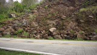 Landslides and rockfalls on the road in the mountains. Mud and rocks blocking the road. Destroyed rural road landslide damaged in powerful flood. Collapsed on the mountain. Philippines, Camiguin. 4K