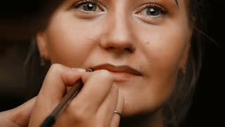 Make-up artist makes make-up young woman lips. Make-up artist doing make-up lip pencil to stroke the lips. Makeup. Cosmetic. Base for Perfect Make-up. Applying Make-up. Lips makeup