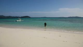 Man in swimsuit walks out on the white sand beach.Travel concept.Family,summer vacation