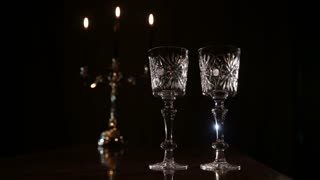 Mystical atmosphere in a dark room with candles, glasses and smoke. Two glasses and candle light at the restaurant. Two wine glasses,burning candles in a chandelier. Romantic atmosphere with wine