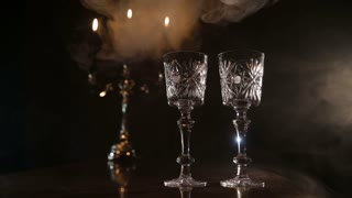 Mystical atmosphere in a dark room with candles, glasses and smoke.Two glasses and candle light at the restaurant.Two wine glasses,burning candles in a chandelier.Romantic atmosphere with wine glasses