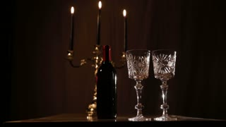 Red wine bottle, two wine glasses,burning candles in a chandelier. Wine glasses on the table, a bottle of red wine and burning candles in a beautiful chandelier behind on a black background. Romantic