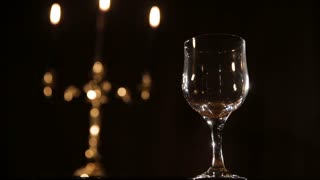 Red wine poured in a glass.Red wine bottle, two wine glasses,burning candles in a chandelier.Pouring red wine into the glass.Wine glasses on the table,and burning candles in a beautiful chandelier
