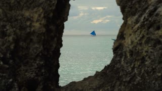 Sailing boat view through a hole in the rock. Sailing ship yachts with blue sails in the ocean. Sail boat on sea. Philippines, Boracay. 4K video. Travel concept