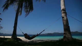 silhouette of man in hammock on the beach.Idyllic beach with coconut trees and hammock.Travel concept