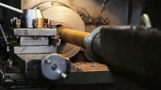 Turning lathe in action. Facing operation of a metal blank on turning machine with cutting tool. Old turning lathe machine in turning workshop. Operator machining high precision mold part by cnc lathe