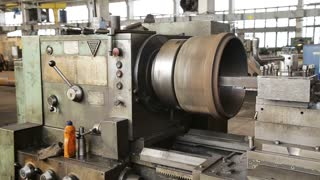 Turning lathe in action.Facing operation of a metal blank on turning machine with cutting tool.Old turning lathe machine in turning workshop.Operator machining high precision mold part by cnc lathe