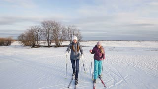Two girls on cross-country skis in the field. Skiing in field in cold winter day. Cross-country skiing on field in the sunny day. Skiers, cross-country skiing in the field at sunset