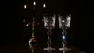 Two glasses and candle light at the restaurant. Two wine glasses,burning candles in a chandelier. Romantic atmosphere with wine glasses and candles