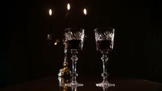 Two glasses of wine clink. Red wine bottle, two wine glasses,burning candles in a chandelier. Wine glasses on the table, a bottle of red wine and burning candles in a beautiful chandelier behind on a