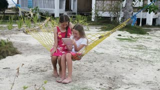 Two young girl relaxing on hammock and using digital tablet.girls in a hammock on a tropical beach and playing with a digital tablet.Travel concept.Family,summer vacation.Happy family