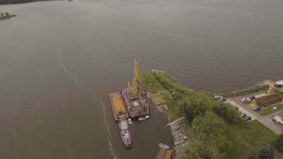 Aerial:port cargo cranes and ship fragment at the docks. Aerial view:Container cranes in cargo port terminal, cargo cranes without job in an empty harbor port. 4K video,ultra HD