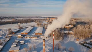Boiler room in the winter season, from the chimneys rise up clouds of steam. Pipes of a thermal power plant. Boiler house, pipe plant, boiler plant. Aerial footage, 4K video.