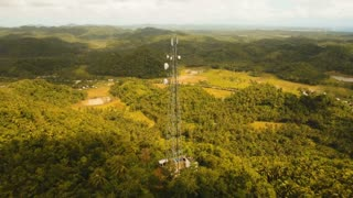 Communication tower, cellphone tower in the jungle in the mountains. Aerial view: satellite, cellphone tower, on a mountain. View of a tropical island with palm trees and other vegetation, a mountain