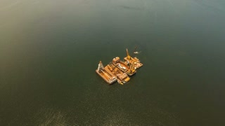 Dredge ship presumably performing harbor and channel maintenance. Aerial view: Huge crane barge Industrial ship that digs sand marine dredging digging sea bottom. Manila, Philippines. Aerial footage