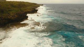 Rocky coast line in time stormy weather on island Siargao. Aerial view sea rocky coast, waves breaking to the rocky shore. Rocky coastline. Big waves crushing on the shore. Philippines. 4K video