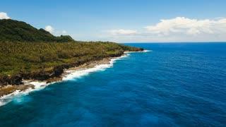 Rocky coast line of Island Siargao. Aerial view sea rocky coast, waves breaking to the rocky shore. Sea landscape, rocks, waves breaking about the shore. Rocky coastline. Philippines. 4K video. Travel
